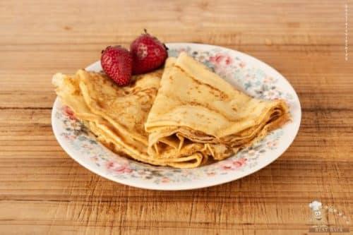 Crêpes auf buntem Teller mit zwei Erdbeeren auf Holztisch - Best-Back Vertrieb - einfach, schnell & vielfältig
